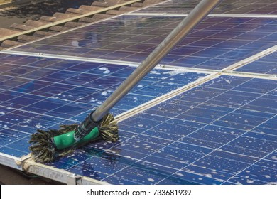 Cleaning solar panels on house roof - Solar Energy Concept Image