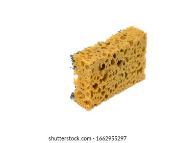 Cleaning sponge with holes, old, on a white background.