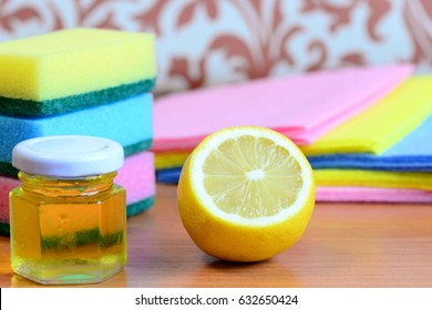 Cleaning sponge with scrub and rags set, olive oil in jar, lemon half on a wooden table. Eco house cleaning idea. Closeup