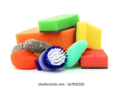 Cleaning sponges and plastic brush on a white background