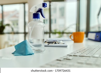 Cleaning spray bottle and a cloth on a desk in the office.