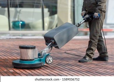 Cleaning staff uses push floor scrubber to clean red floor tiles