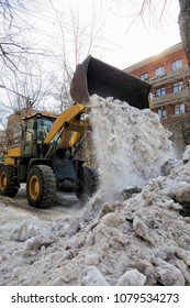 Cleaning the streets of snow, tractor clears banks.