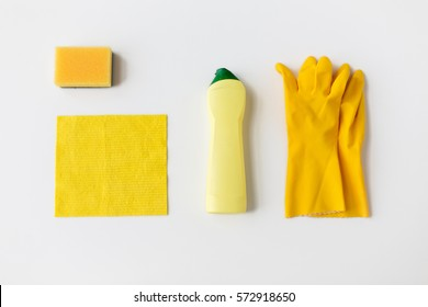 cleaning stuff, housework, housekeeping and household concept - bottle of detergent, rubber gloves with rag and sponge on white background