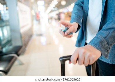 Cleaning suitcase luggage handle with hand sanitizer spray. Male tourist spraying antibacterial product to his carry-on bag in airport terminal. Coronavirus (COVID-19) prevention during travel