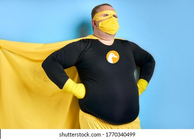 cleaning superhero saves the world from dirt, man has duck picture on costume, he is in yellow wear and in protective gloves, posing isolated over blue background