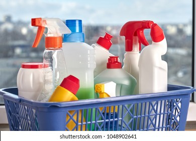 Cleaning supplies on wooden background. Set of cleaning products in blue plastic basket close up.