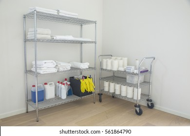 Cleaning supplies and tools (towels) arranged on shelves made of steel at home.