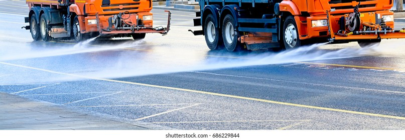 Cleaning sweeper machines washes the city asphalt road with water spray.