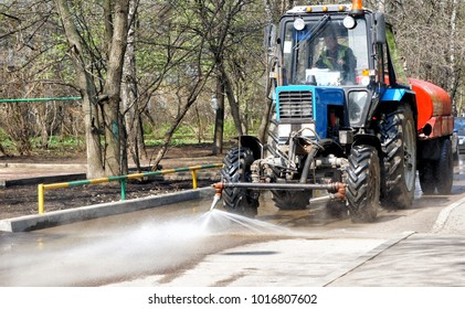 Cleaning sweeper tractor pours water on the asphalt, cleaning the city street.