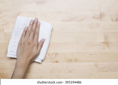 Cleaning table by woman hand