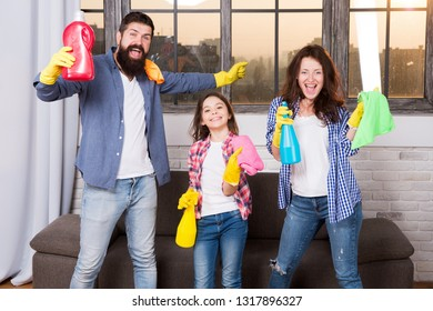 Cleaning together easier and more fun. Family care about cleanliness. Start cleaning. Cleaning day. Family mom dad and daughter with cleaning supplies at living room. We love cleanliness and tidiness.
