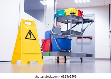 Cleaning trolley with yellow wet floor caution sign