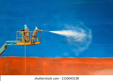 Cleaning Two People worker in floating dock during washing by Pressure washer boat hull barnacles wear equipment protective safety harness on high sherry picker car before ship repair with sand blast