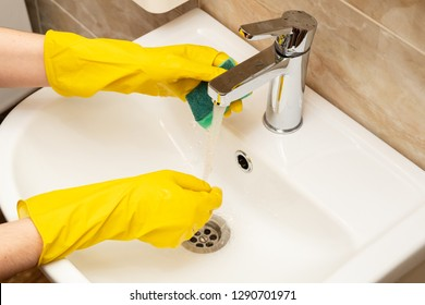 Cleaning washbasin, cleaning service concept. Woman's hands in yellow protective rubber gloves with green sponge under running water from a stainless steel tap on a white ceramic hand basin.