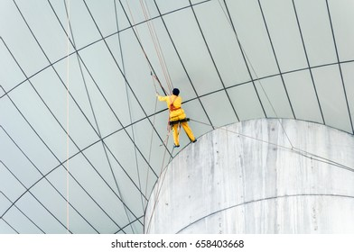Cleaning windows service on high rise building. The man climber or Spider man which clean or wipe glass and exterior wall of skyscraper that it is dangerous work for Professional worker.