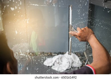 Cleaning windows with a squeegee.
