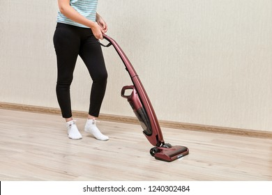 Cleaning woman in black leggins is vacuuming with help of upright vacuum cleaner with led lights on.