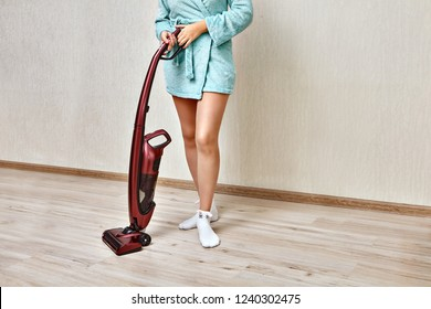 Cleaning woman in a blue home robe is holding a red handheld vacuum cleaner in an empty room.