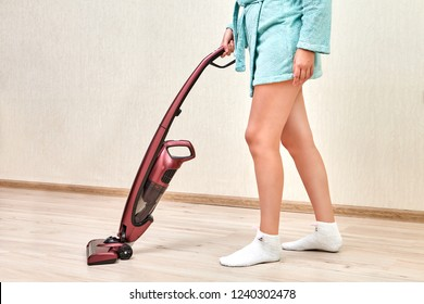 Cleaning woman in a blue robe is vacuuming in an empty room with laminated floor using a cordless handheld vacuum.