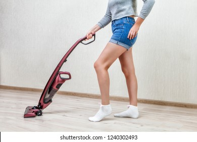 Cleaning woman in denim shorts is vacuuming with help of red modern cordless handheld vacuum with led lights on.