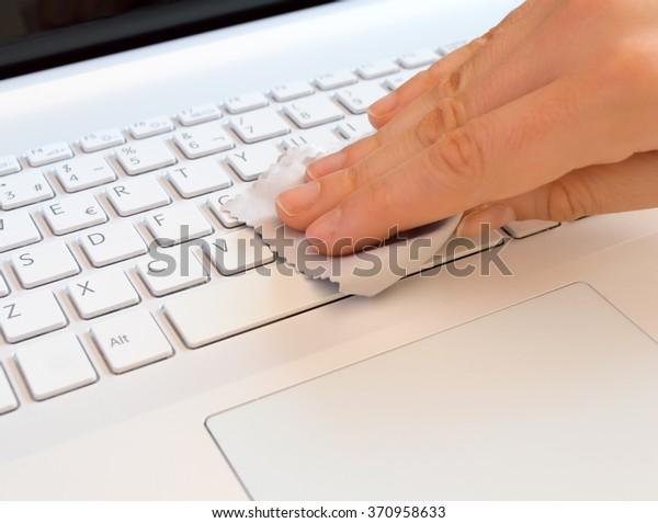 mujer limpiadora con un trapo gris de un teclado de computadora