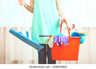 A cleaning woman with a mop for washing floors and a bucket with cleaning products.