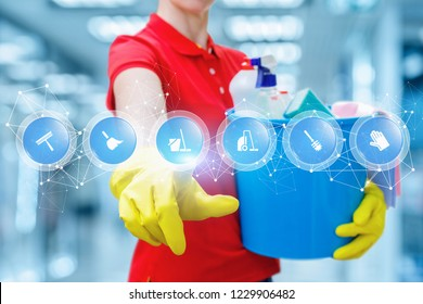 A cleaning woman in rubber gloves is keeping a bucket fulfilled with chemicals and touching a screen with digital scheme of many symbols. The concept is the popularity of cleaning service.