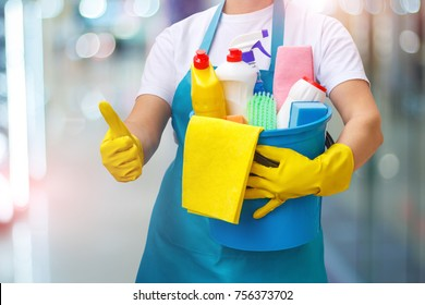 Cleaning woman shows up the quality of the cleaning on blurred background.