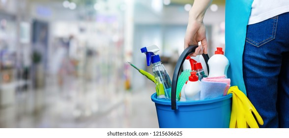 A cleaning woman is standing inside a building holding a blue bucket fulfilled with chemicals and facilities for tidying up in her hand.