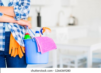A cleaning woman is standing inside a building holding a blue bucket fulfilled with chemicals and facilities for tidying up in her hand