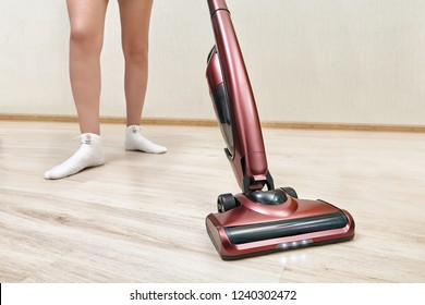 Cleaning woman is vacuuming in an empty room using a handheld vacuum cleaner with lights on.