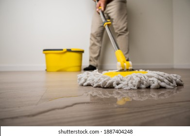 Cleaning workers mopping the wet area. There was spill water on the wooden floor in the living room.