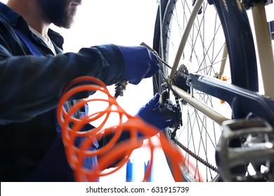 Cleaning your bicycle with compressed air. The mechanic in the bike service cleans the bicycle with compressed air.