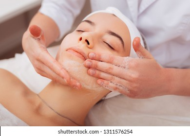 Cleansing foam. Nice beautiful woman lying on the bed while having her face cleansed with foam