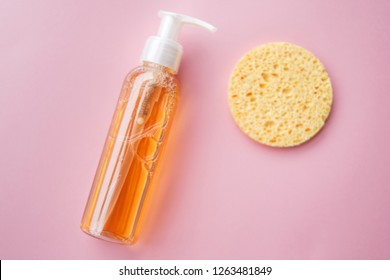 cleansing oil for the face or cleansing gel with oils. skin cleaning, makeup removal, facial cleanser, washing, pink background. selective focus