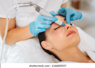 Cleansing procedure. Nice pretty woman lying with her eyes closed while having a cleansing procedure on her face