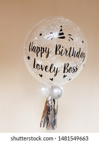"""Clear balloon decorated the lovely words""""Happy Birthday Lovely Boss"""" on light brown background"""