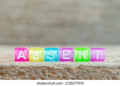 Clear bead with white letter in word absent on wood background