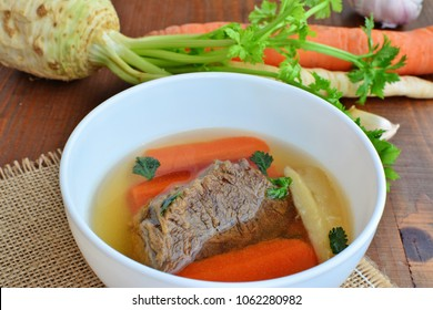 Clear beef broth, bone broth, bouillon with boiled meat and vegetables on wooden table top view