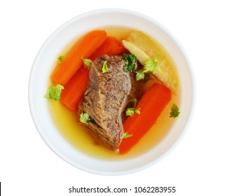 Clear beef broth, bone broth, bouillon with meat and vegetables in white bowl isolated, top view