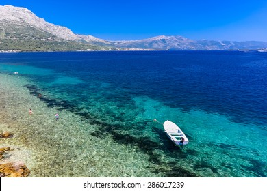 Clear blue beach at Korcula Croatia with boat and mountain and people swimming