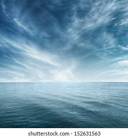 Clear blue sea and cloudy sky over it
