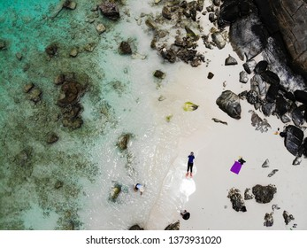 Clear blue sea on a white beach with rocks from high angle photos