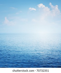 Clear blue sea surface with ripples and sky with fluffy clouds