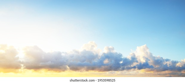 Clear blue sky with glowing pink and golden cumulus clouds after storm at sunset. Dramatic cloudscape. Concept art, meteorology, heaven, hope, peace, graphic resources, picturesque panoramic scenery - Shutterstock ID 1953598525