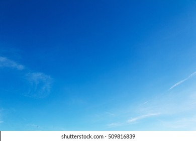 Clear blue sky with light white clouds and trails