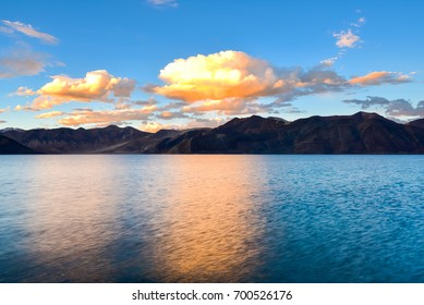 Clear blue sky and water with brown mountains in background at sunset time, Pangong tso