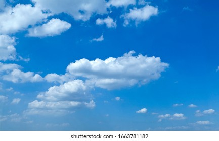 A clear blue sky with white clouds