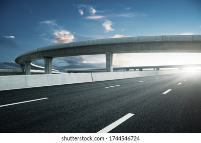 Clear blue sky and white clouds in the background, highway overpass curved approach bridge